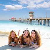 happy three teen friends girls lying on beach sand smiling at Huntington Beach California  [ photo-i