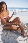 Smiling woman  on the beach applying sun cream on her leg