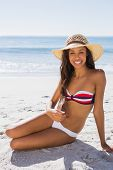 Sexy young tanned woman wearing straw hat posing on the beach