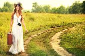 Romantic smiling young woman in a circlet of flowers goes on a country road with her old camera and