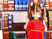 stock photo of knapsack  - Child with backpack reading book in library - JPG