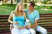 Pregnant woman with man  holding teddy bear outdoor in park.