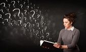 stock photo of laws-of-attraction  - Confused woman reading a book with question marks coming out from it - JPG