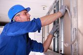 stock photo of voltage  - Electrician installing wiring - JPG