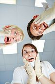 Dentists during dental treatment looking shocked at patient POV