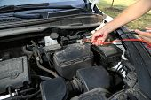 image of dead-line  - Car mechanic uses battery jumper cables to charge dead battery - JPG