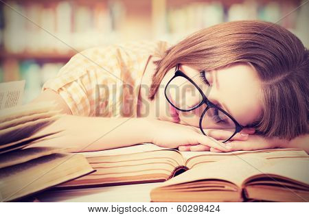 Tired Student Girl With Glasses Sleeping On Books In Library poster