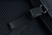 image of sling bag  - Black plastic buckle with strap on backpack - JPG