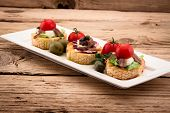 Crostini Vith Mozzarella Cheese Anchowy And Tomato