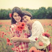 Attractive middle-aged woman have fun on a poppy field with her, summer outdoor. Image toned.