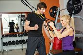 personal trainer with client at gym