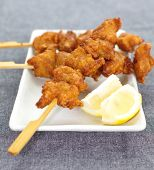 Fried chicken with skewer on white plate