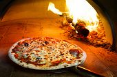 stock photo of flame  - Close up pizza in firewood oven with flame behind - JPG
