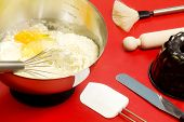 stock photo of confectioners  - cake mixture and confectioner utensils over red - JPG