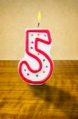 Burning birthday candle number 5 on a wooden background