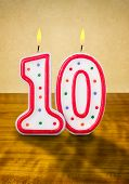 Burning birthday candles number 10 on a wooden background
