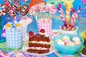 stock photo of tort  - slice of chocolate torte with candle and homemade sweets for children birthday party