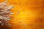 Ears of wheat on old wooden table.