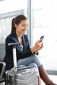 stock photo of carry-on luggage  - Airport woman on smart phone at gate waiting in terminal - JPG