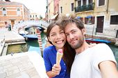 Couple in Venice, eating Ice cream taking selfie self-portrait photo on vacation travel in Italy. Smiling happy Asian woman and Caucasian man in love having fun eating italian gelato food outdoors.