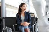 Airport woman waiting in terminal. Air travel concept with young casual business woman sitting with carry-on hand luggage trolley in airport lounge. Beautiful young mixed race female professional