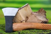 Ax and firewood on green grass, on nature background