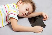 Little tired sleeping child boy hand holding digital tablet computer