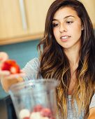 Beautiful Young Woman Making Fruit smoothie