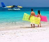 Couple with inflatable rafts looking at arrived seaplane on a tropical beach at Maldives. No brand n