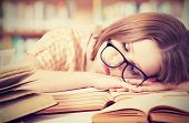 image of sleeping  - tired student girl with glasses sleeping on the books in the library