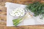 Metal bowl of cream with a tuft of onion, dill and parsley in a basket near it on a napkin on wooden