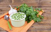 Plastic round bowl of cream with a tuft of parsley and garlic near it on an orange napkin on wooden