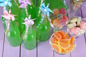 Bottles with drink and sweets on wooden background