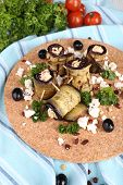 Fried aubergine with cottage cheese and parsley on a round cutting board on a napkin
