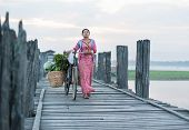 MANDALAY, MYANMAR - JAN 19, 2014: Unidentified young woman in traditional dress crossing U Bein brid