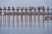 MANDALAY, MYANMAR - JAN 18, 2014: Unidentified people crossing famous U Bein bridge. The place is one of most visited sights in Burma