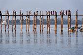 MANDALAY, MYANMAR - JAN 18, 2014: Unidentified people crossing famous U Bein bridge. The place is on