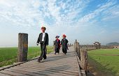 MANDALAY, MYANMAR - JAN 19, 2014: Unidentified group of people from Burmese ethnic minority crossing U Bein bridge. The place is known as one of most honored among citizens of Burma