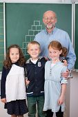 Elderly Male Teacher With Three Young Students