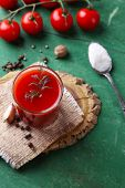 Homemade tomato juice in glass, spices and fresh tomatoes on wooden background