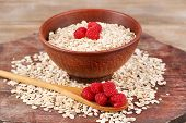 Big brown bowl with oatmeal and berries on a wooden table