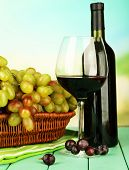 Ripe grapes in wicker basket, bottle and glass of wine, on bright background