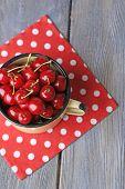 Sweet cherries in mug on wooden background