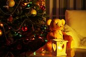 Teddy bear in home interior on Decorated Christmas tree background