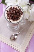 Yogurt, with chocolate cream, chopped chocolate and muesli served in glass on color  wooden backgrou