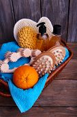 Shower kit in a brown rectangular basket on wooden table in front of wooden wall