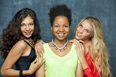 Ethnic three women face - isolated on dark wall
