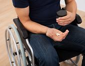 Man Holding Medicine While Sitting On Wheelchair