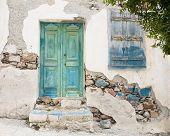Old Wooden Door Of A Shabby Demaged House Facade Or Front.