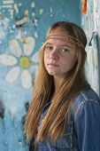 Portrait of young cute girl hippie, dirty painting background.